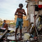 RIO DE JANEIRO, BRAZIL - MAY 22: A man bathes from a small hose amongst the remains of demolished homes in the Metro Mangueira favela, located near Maracana stadium, on May 22, 2014 in Rio de Janeiro, Brazil. The homes were thought to have been knocked down for a parking lot for the stadium, though that has yet to be built. The area has seen some people occupy certain dwellings. Evictions and demolitions have been occurring in Rio favelas ahead of the 2014 FIFA World Cup and Rio 2016 Olympic Games in spite of a housing shortage in the city. Rio's housing and urban planning goals include a planned five percent reduction of areas occupied by favelas by 2016. Alternative affordable housing, generally on the peripheries of the city, is unable to meet demand and some residents complain they have not received adequate compensation for demolished homes. (Photo by Mario Tama/Getty Images)